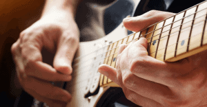 Man playing a guitar close up
