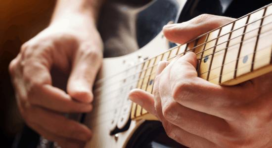 Man playing a guitar close up