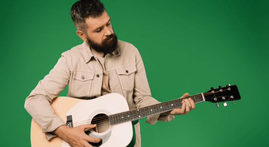 person with beard playing guitar