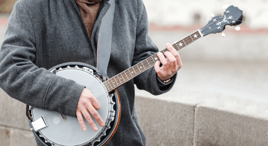 man playing banjo outside