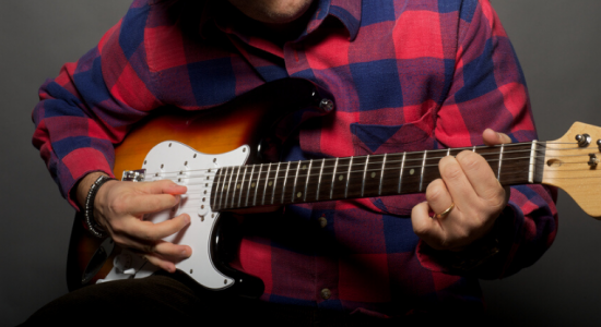 guy playing stratocaster guitar