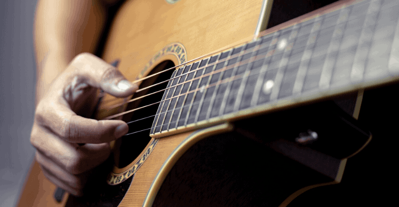 person playing fingerstyle guitar