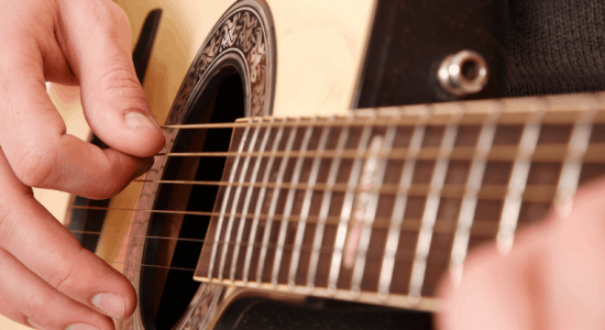 Person strumming an acoustic guitar