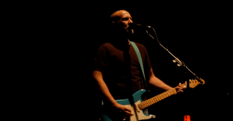 Guy playing guitar and signing