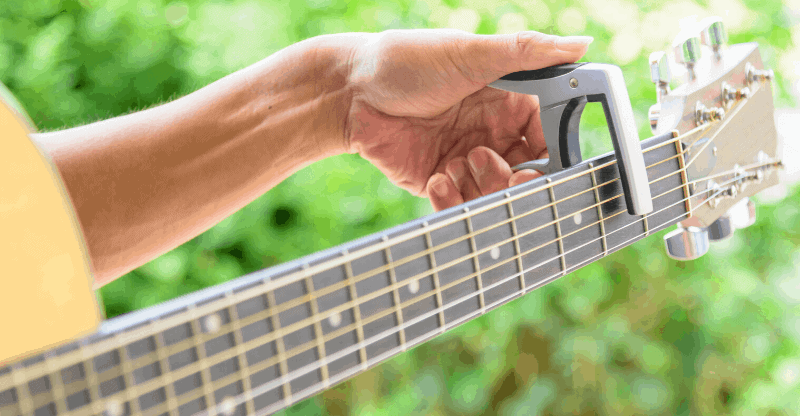 Person putting a capo on a guitar
