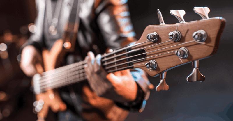 man playing 5 string bass guitar