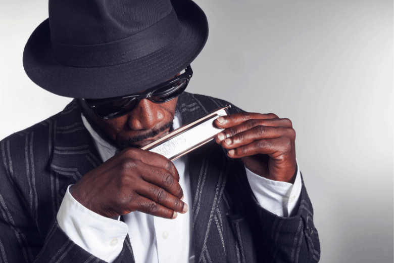 Black man with hat and shades playing the harmonica