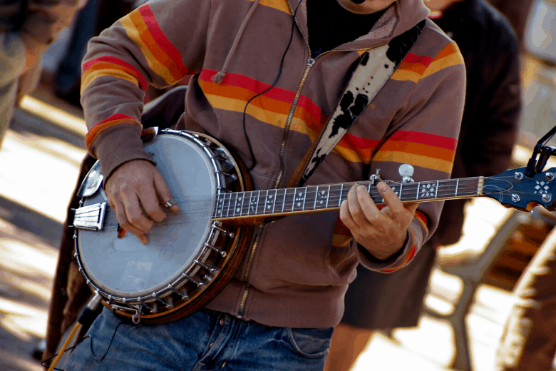 Person in hoody playing banjo on the street
