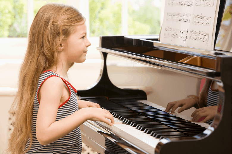Young girl with long hair playing an upright piano and reading sheet music