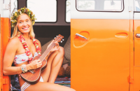 girl playing ukulele in campervan