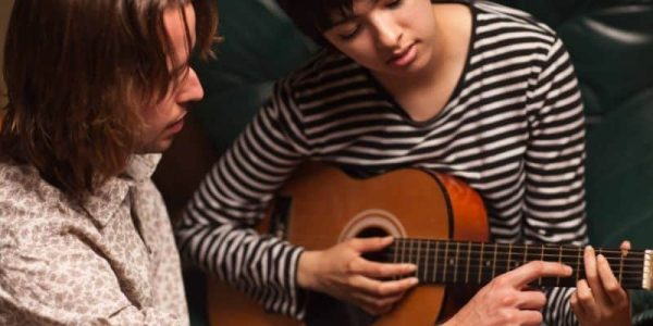 teacher and girl learning to play guitar