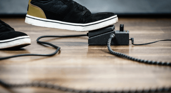 Person pressing guitar pedal with foot
