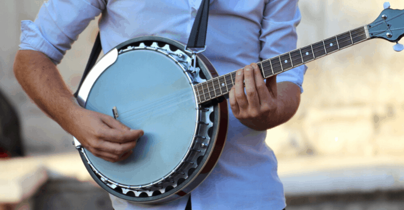guy playing banjo in street