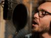 Man singing in a recording studio wearing headphones