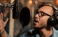 Man singing in a recording studio wearing headphones