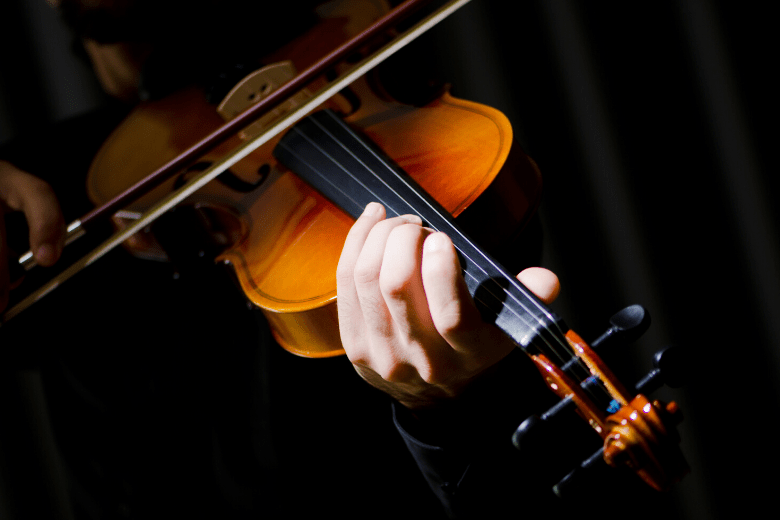 Close up person playing violin