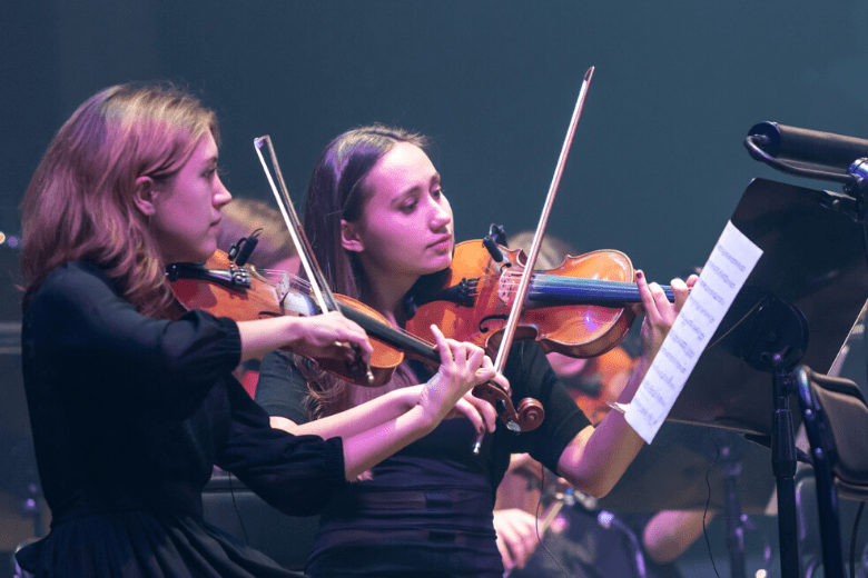 Two women playing violin