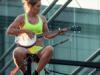 Woman playing banjo balanced on fence