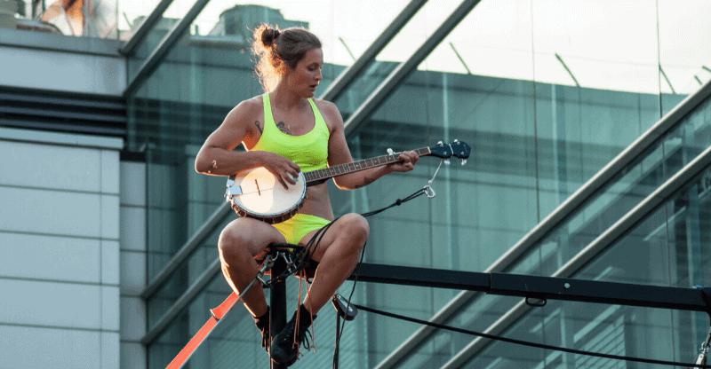 Woman playing banjo balanced on fence