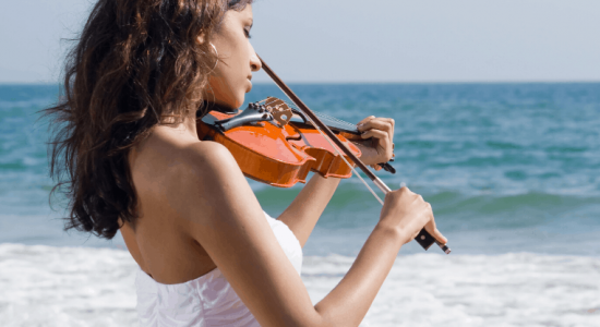 girl playing violin on the beach