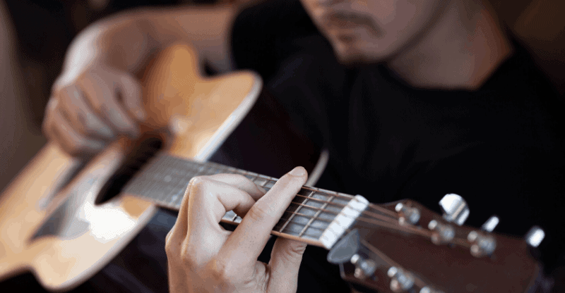 guy playing a barre chord