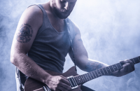 guy with tattoo playing guitar