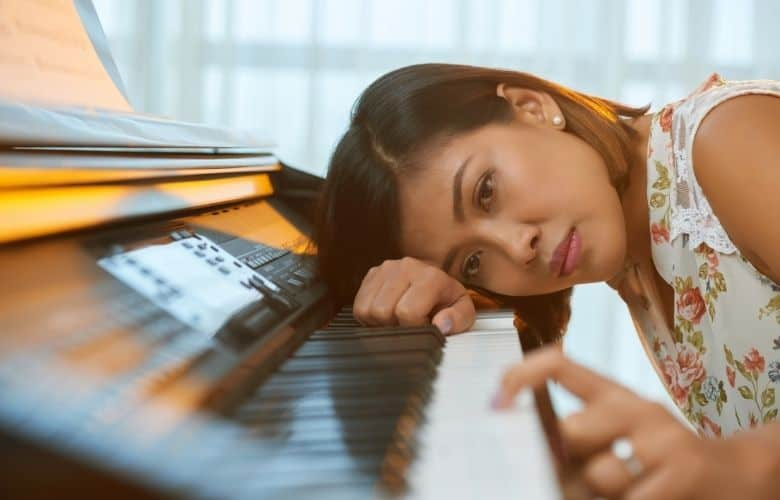 Tired woman sat at the piano