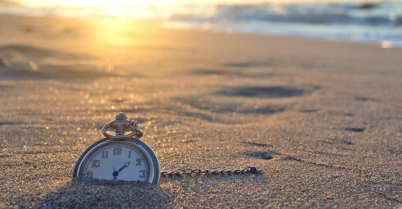 clock merged in sand