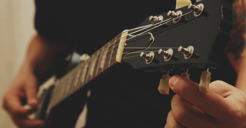close up of person tuning a guitar
