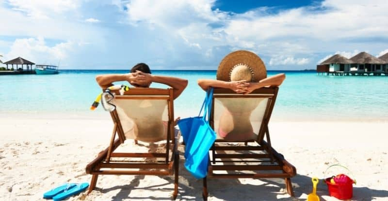 couple on sunbeds on a beach