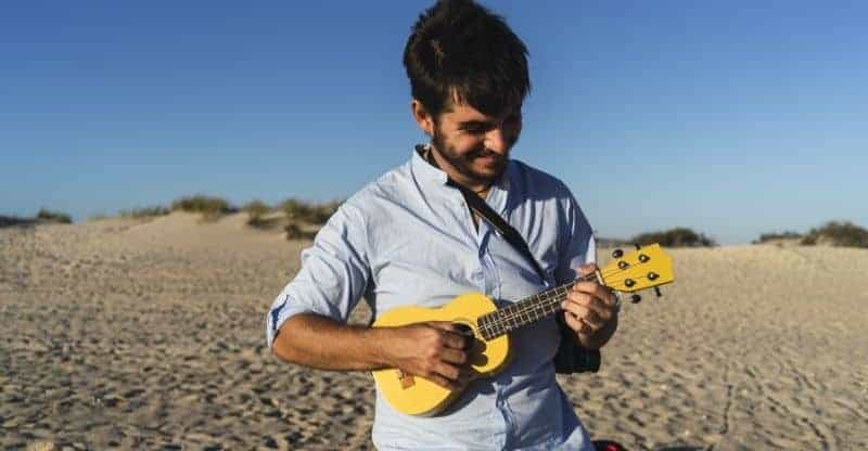 guy strumming a uke on a beach
