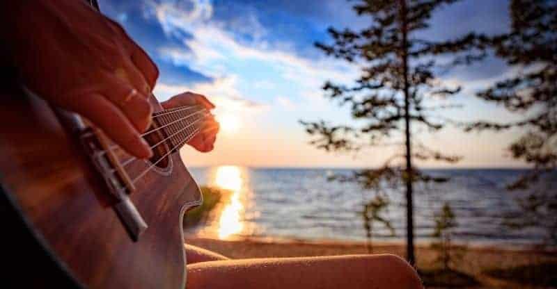 person playing ukulele at sunset