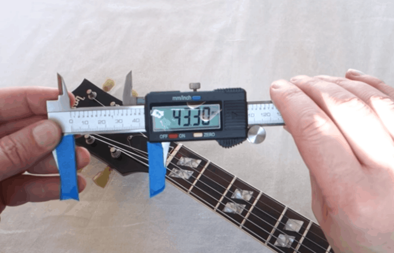 using a caliper to measure nut width on an electric guitar