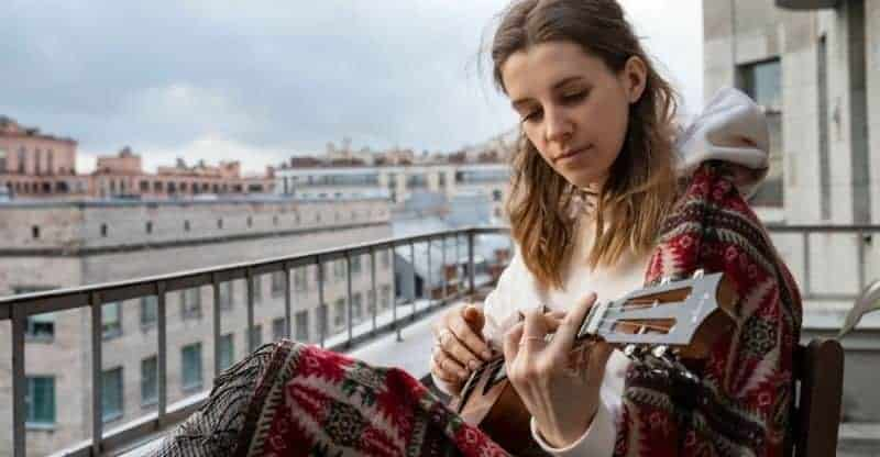 woman playing a barre chord on the ukulele